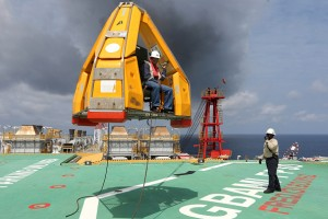 An oil worker is transferred via a 'Frog' basket from the tugboat Bourbon Auroch, operated by Bourbon SA, onto the deck of the Agbami floating production, storage and offloading vessel (FPSO), operated by Chevron Corp., in the Agbami deepwater oilfield in the Niger Delta, Nigeria, on Monday, Nov. 16, 2015. Nigeria plans to review agreements for deep offshore oil production to seek more favorable terms in line with the latest industry standards, state-owned Nigerian National Petroleum Corp. said. Photographer: George Osodi/Bloomberg via Getty Images