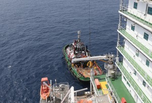 Workers are transferred via a 'Frog' basket from the tugboat Bourbon Auroch, operated by Bourbon SA, onto the deck of the Agbami floating production, storage and offloading vessel (FPSO), operated by Chevron Corp., in the Agbami deepwater oilfield in the Niger Delta, Nigeria, on Monday, Nov. 16, 2015. Nigeria plans to review agreements for deep offshore oil production to seek more favorable terms in line with the latest industry standards, state-owned Nigerian National Petroleum Corp. said. Photographer: George Osodi/Bloomberg via Getty Images