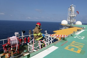 A firefighter sits on the edge of the helideck as he waits for a helicopter to arrive on the Agbami floating production, storage and offloading vessel (FPSO), operated by Chevron Corp., in the Agbami deepwater oilfield in the Niger Delta, Nigeria, on Monday, Nov. 16, 2015. Nigeria plans to review agreements for deep offshore oil production to seek more favorable terms in line with the latest industry standards, state-owned Nigerian National Petroleum Corp. said. Photographer: George Osodi/Bloomberg via Getty Images